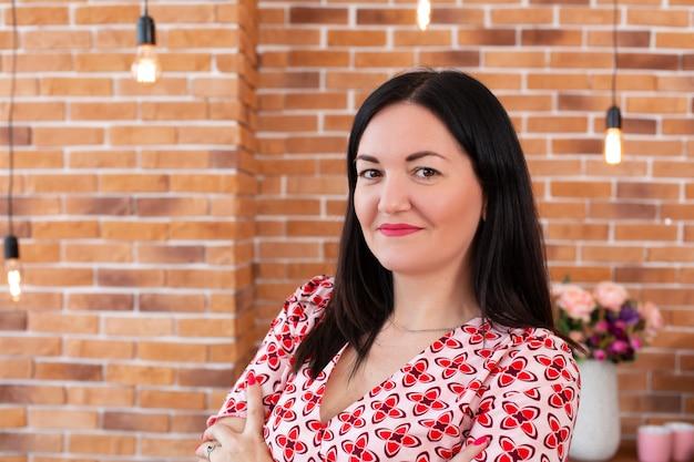メガネの専門のかかりつけ医心理学者はロフトスタイルでオフィスに座って、カメラに笑顔します。心理療法。女性心理療法士の肖像
