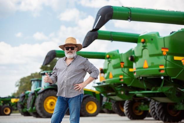 현대 트랙터가 있는 전문 농부는 직장에서 햇빛이 비치는 들판에서 결합합니다. 농업, 전시, 기계, 식물 생산. 그의 기계 근처 수석 남자입니다.