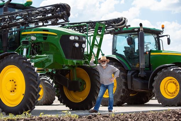 현대 트랙터가 있는 전문 농부는 직장에서 햇빛이 비치는 들판에서 결합합니다. 자신감 있고 밝은 여름 색상. 농업, 전시, 기계, 식물 생산. 그의 기계 근처 수석 남자입니다.