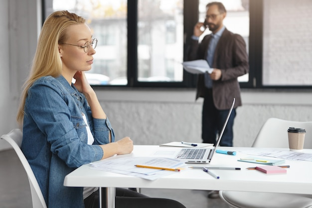 Professional female analyst sits at work desk surrounded by papers