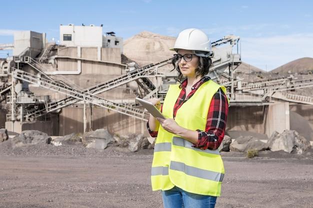Профессиональная женщина-архитектор в каске и жилете проверяет проект на планшете, стоя возле промышленного объекта строительной площадки