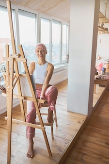 バルコニーのイーゼルで新しい描画に取り組んでいるプロの女性アーティスト