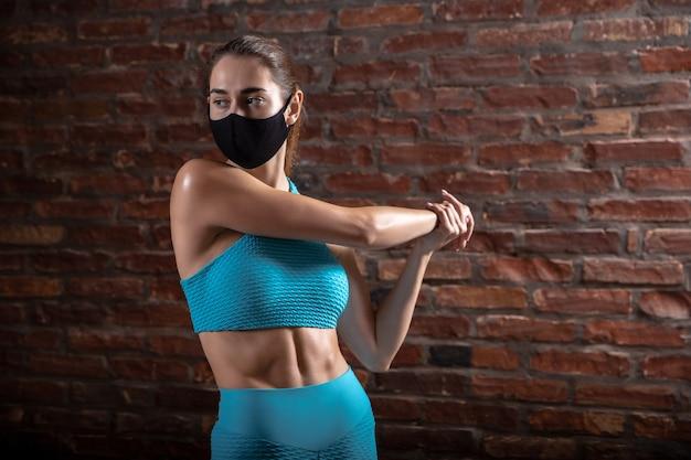 Professional female athlete training on brick wall wearing face mask.