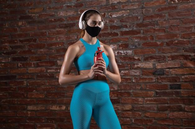 얼굴 마스크를 쓰고 벽돌 벽 배경에서 훈련하는 전문 여성 운동선수.