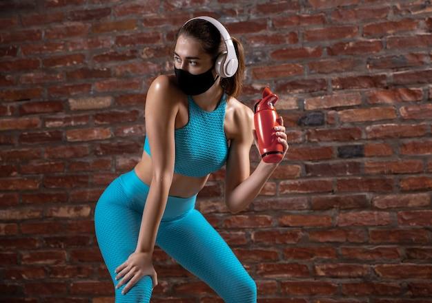 얼굴 마스크를 쓰고 벽돌 벽 배경에서 훈련하는 전문 여성 운동선수