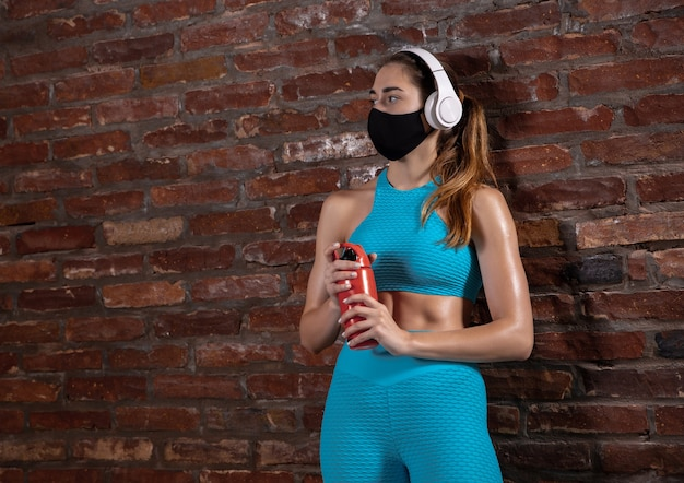 얼굴 마스크를 쓰고 벽돌 벽 배경에서 훈련하는 전문 여성 운동 선수
