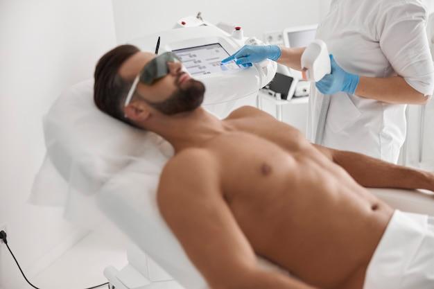 Профессиональный косметолог настраивает современное оборудование для лазерной эпиляции