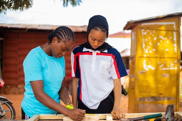 전문 여성 목수와 그녀의 견습생이 신중하게 측정