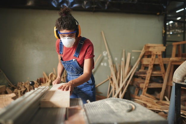 Профессиональная женщина-плотник в защитных очках, наушниках и маске, режущая деревянную доску на настольной пиле