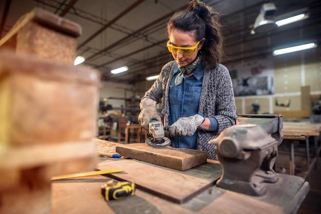 Профессиональный плотник женского пола, работающий наждачной бумагой в своей мастерской