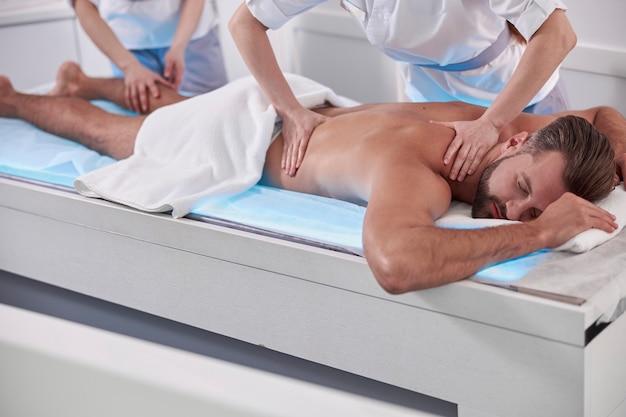 전문 여성 카이로프랙틱은 성숙한 수염 난 남자 환자에게 등과 다리 마사지를 한다