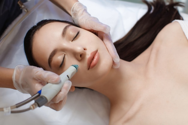 Professional female cosmetologist doing hydrafacial procedure