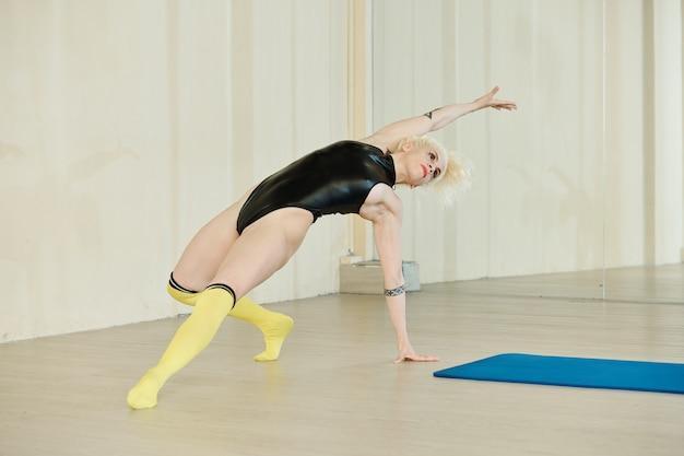 革のレオタードとニーハイソックスのプロの女性ダンサーがダンスクラスの床で新しい難しい動きを賞賛