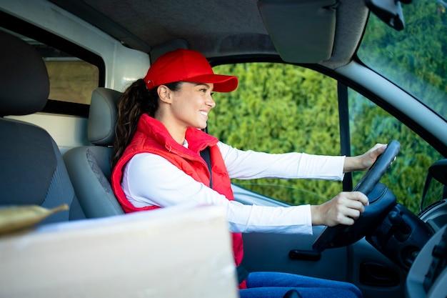 Профессиональный работник службы доставки женского пола за рулем своего фургона с пакетами со склада по адресу.