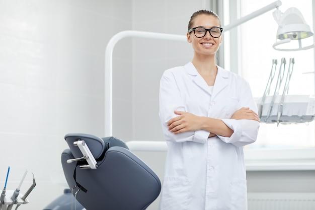 Профессиональный женский стоматолог позирует в офисе