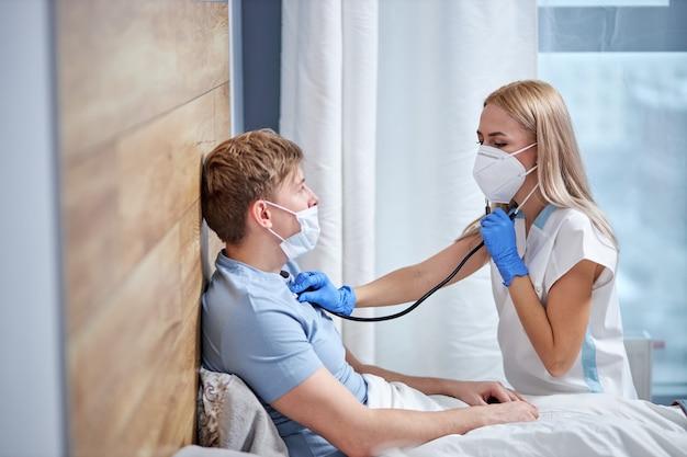 Профессиональная женщина-врач слушает дыхание пациента мужского пола с помощью стехоскопа, дома, лежа на кровати, страдающего симптомами коронавируса. covid-19. концепция медицины