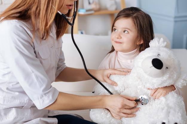 聴診器を使用し、ソファに座ってふわふわのクマを調べる専門の女性医師