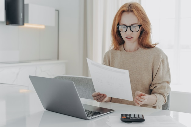 Professional female economist calculates finance at home holds paper document makes financial report