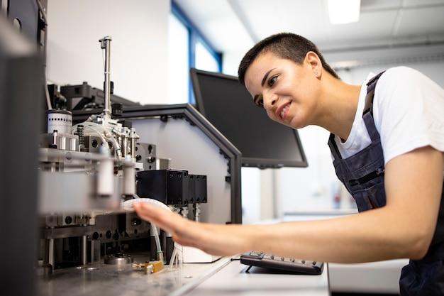 공장에서 산업 기계를 서비스하는 전문 여성 엔지니어.