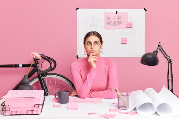 Professional female engineer thinks over ideas for building project has thoughtful expression wears round spectacles and turtleneck poses in coworking space against pink wall blueprint behind