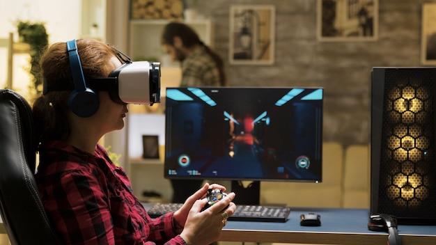 Vr 헤드셋과 무선 컨트롤러를 사용하여 컴퓨터 게임을 하는 전문 여성 게이머. 백그라운드에서 전화로 문자를 보내는 남자.