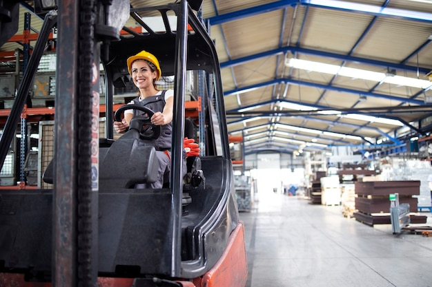 工場のホールでフォークリフトを操作するプロの女性産業ドライバー