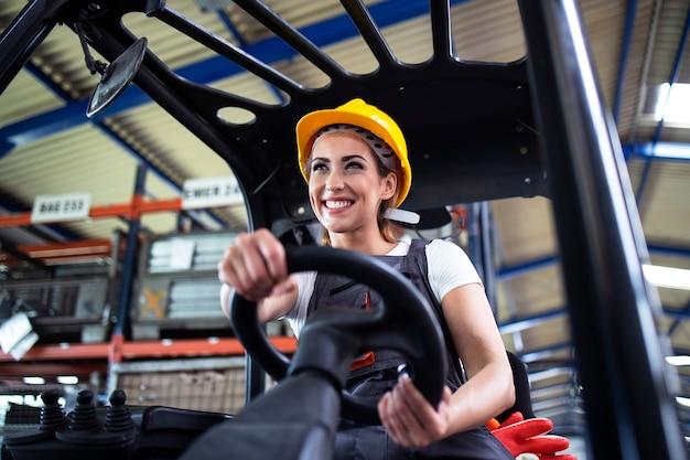 工場の倉庫でフォークリフトを操作するプロの女性産業ドライバー