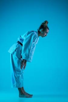 네온에서 파란색 스튜디오 배경에 고립 된 포즈를 취하는 전문 여성 유도