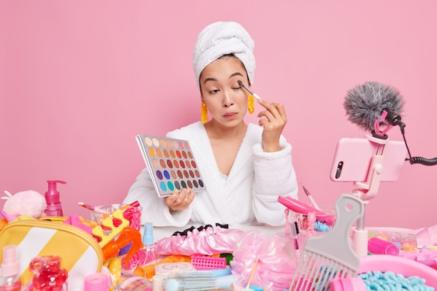 Professional female makeup artist applies shadow on eyes holds colorful palette uses cosmetic tools and products records live stream video on smartphone