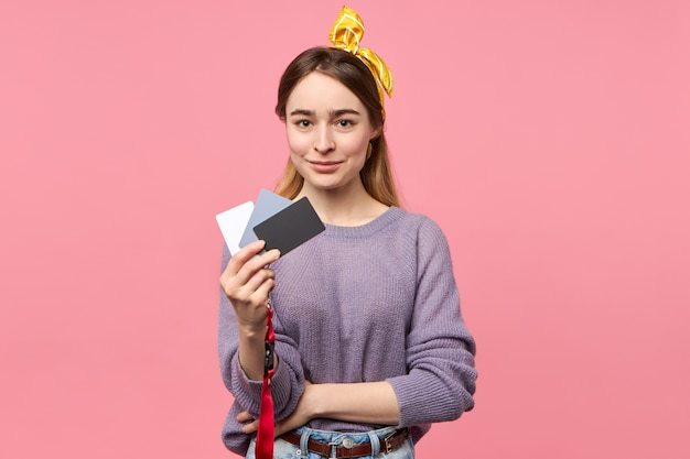 Professional female photographer holding white, gray and black cards to adjust exposure and white balance settings