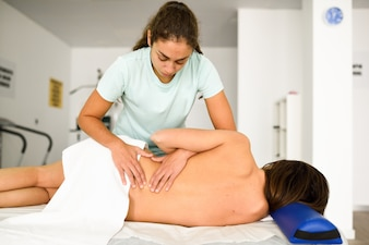 Professional female physiotherapist giving lumbar shoulder massage to a woman
