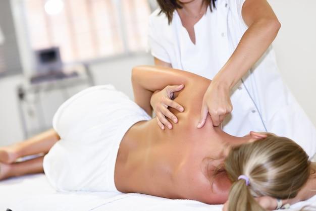 금발의 여자에게 어깨 마사지를주는 전문 여성 물리 치료사