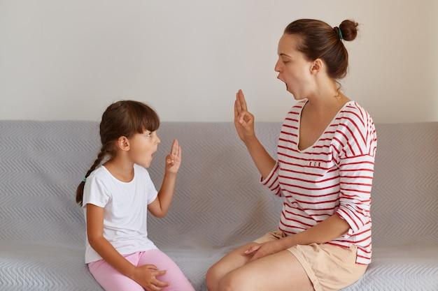 Fisioterapista professionista femminile che lavora su difetti del linguaggio o difficoltà con una bambina piccola al chiuso mentre è seduto sul divano, un bambino piccolo che ha lezione di lingua per migliorare la conversazione.