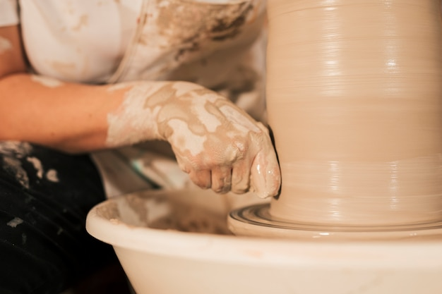 Professional female potter smoothing clay on potter's wheel