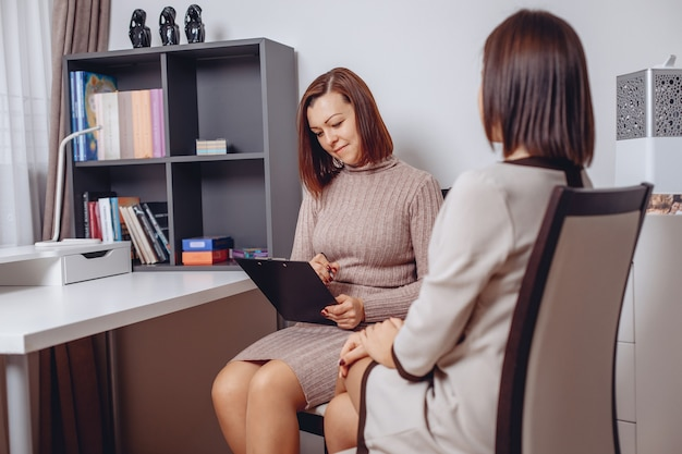 Professional female psychologist sitting at the table and listening to the girl's complaints while looking at her and taking notes.