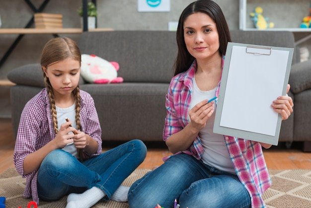 Professional female psychologist sitting with girl on carpet showing white paper on clipboard