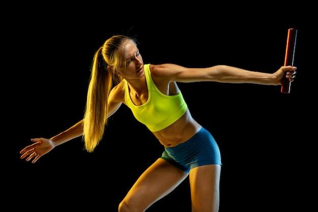 Professional female relay racer training on black studio