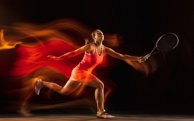 Professional female tennis player isolated on black studio wall in mixed light