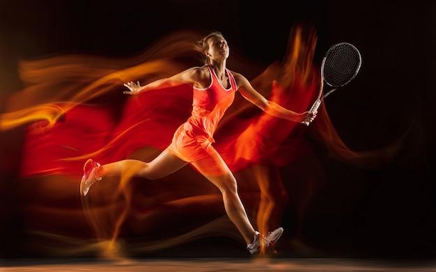 Giocatore di tennis femminile professionista formazione isolato su sfondo nero studio in luce mista. donna in tuta sportiva che pratica.