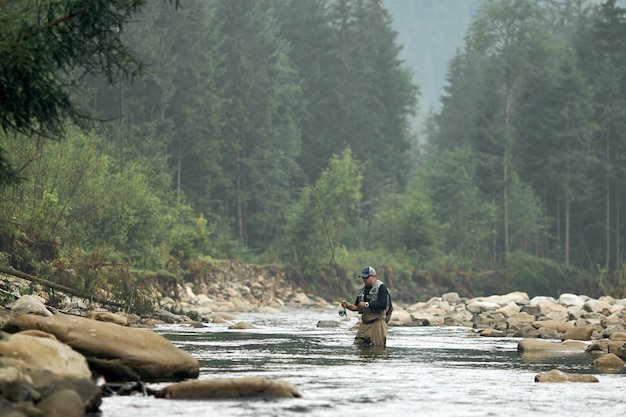 Professional fisherman standing in water with fishing rod and trying to catch fish. amazing natural landscape on wall. mountain river.