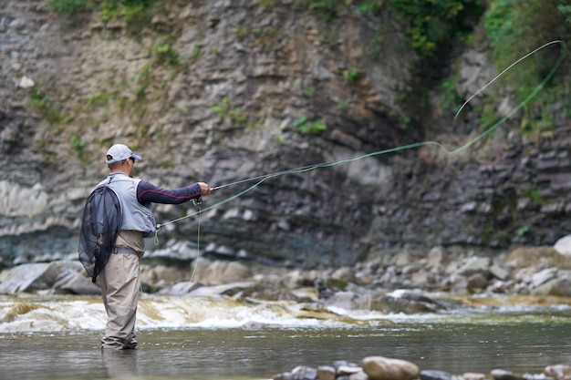 Professional fisherman in waterproof outfit throwing rod into rough river among mountains. beautiful summer nature around. concept of fishery.