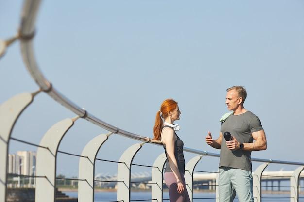 堤防の上に立って赤毛の女性とトレーニングについて話し合う水筒を持つプロのフィットネスコーチ