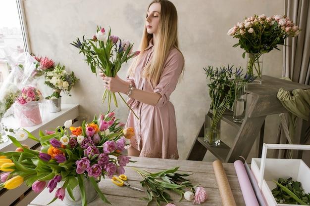 フラワーショップのプロの花屋デコレーターが新しい花束を作ります。チューリップの品揃え、アーティストの職場で働く女性