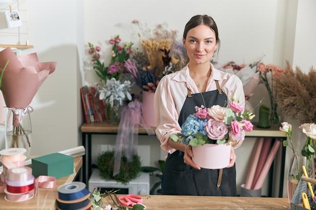 Молодая женщина профессиональный флорист делает букеты в цветочном магазине