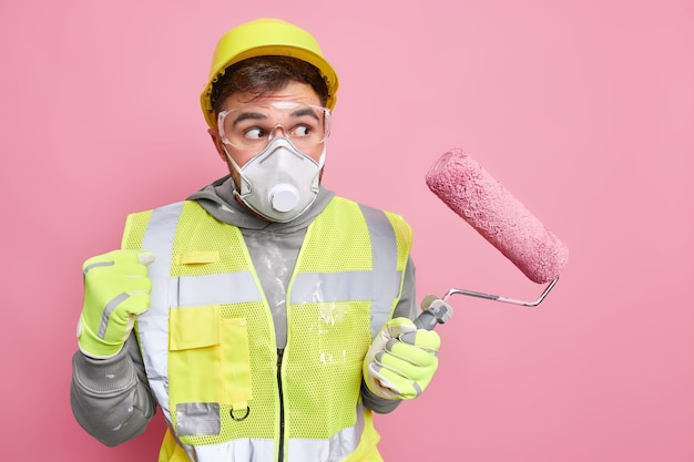 Professional foreman or construction worker in protective helmet face mask and uniform holds paint roller clenches fist