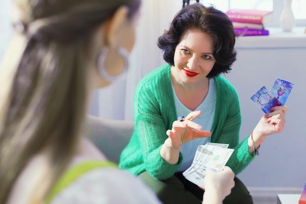 Профессиональное мошенничество. милая хитрая женщина смотрит на своего посетителя, обманывая ее