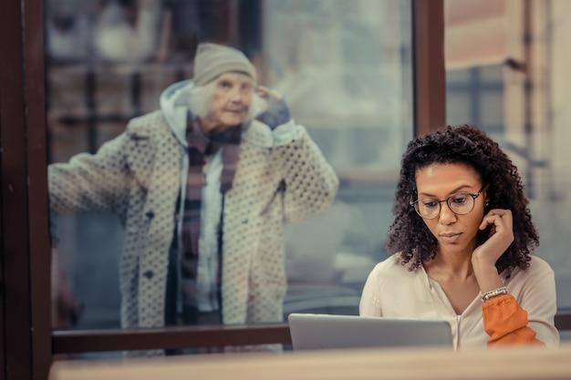 プロのフリーランサー。彼女の後ろにホームレスの女性に気づかずにラップトップで作業している素敵な若い女性