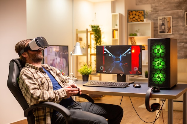 Professional gamer man using vr headset to play on powerful pc late at night in his living room