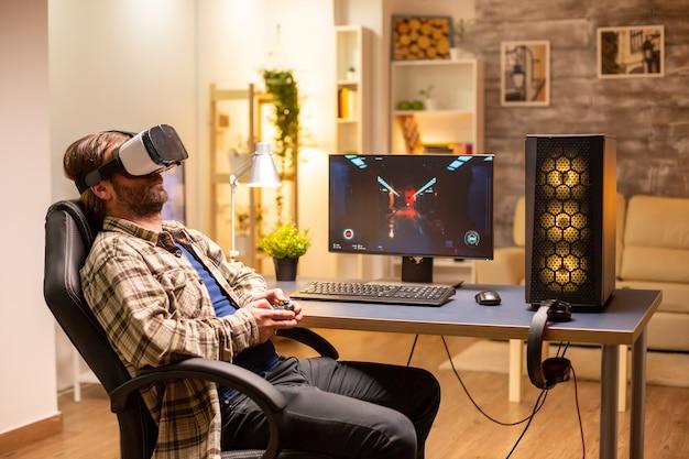 Профессиональный геймер, использующий гарнитуру vr, чтобы играть на мощном пк поздно ночью в своей гостиной