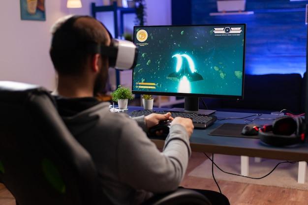 仮想現実のヘッドセットを着用し、コントローラーでスペースシューティングビデオゲームをプレイするプロのゲーマー。ネオンライトのある部屋でeスポーツトーナメントのオンラインビデオゲームをストリーミングする男